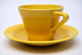 Vintage Harlequin Pottery Yellow Cup and Saucer Set For Sale